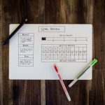 actively review your goals - goals sheet with pens