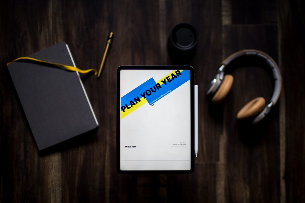 why set smart goals - tablet, notebook, headphones and pen